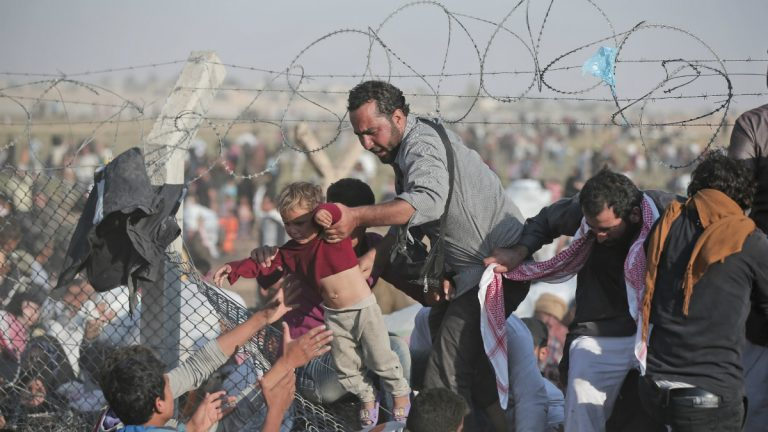 FILE - A Sunday, June 14, 2015 file photo of a Syrian refugee carrying a baby over the broken border fence into Turkey (AP Photo/Lefteris Pitarakis, File)