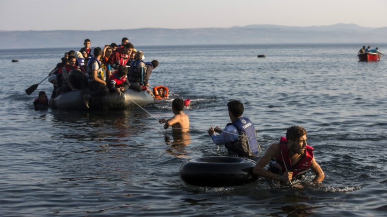 Migrants pull an overcrowded dinghy with Syrian and Afghan refugees arriving from the Turkish coasts to the Greek island of Lesbos, Monday, July 27, 2015. (AP Photo/Santi Palacios)