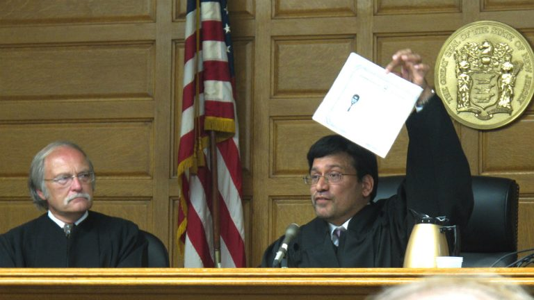 In this photo of July 26, 2011, Sohail Mohammed holds up a copy of his citizenship papers at his ceremonial swearing in ceremony as a New Jersey Superior Court judge in Paterson, N.J. (AP Photo/Wayne Parry)