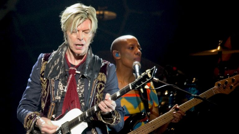 Rock vocalist David Bowie, left, performs at the Fleet Center in Boston, Tuesday, March 30, 2004. (AP Photo/Robert E. Klein)