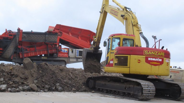 Heavy equipment shores up an earthen barrier where a street end meets the beach in Bay Head
