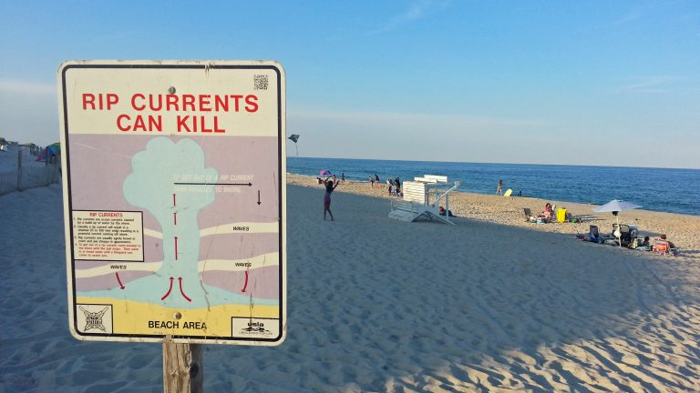A sign in Cape May instructs swimmers caught in a rip current to swim parallel to the beach to escape. (Alan Tu/WHYY)