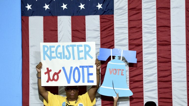 Participants carry signs at a voter registration event in West Philadelphia in August. (Bastiaan Slabbers for NewsWorks)