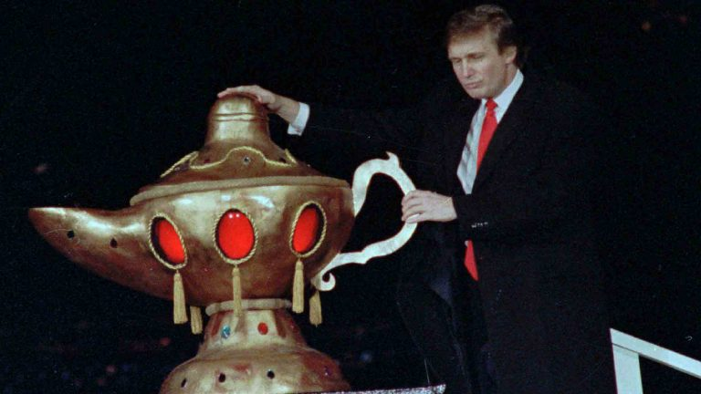 Donald Trump rubs a genie's lamp during grand opening ceremonies for the Trump Taj Mahal Casino Resort in Atlantic City April 6