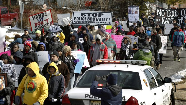 People hold signs and shout as they march in protest of a recent fatal police shooting Saturday