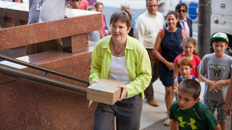 Fired teacher Margie Winters delivers petitions signed by more than 20,000 supporters who are seeking to have her reinstated at Waldron Mercy Academy. Winters, who was let go because of her same-sex marriage, handed the pleas to a Archdiocese of Philadelphia security guard.(Brad Larrison/for NewsWorks)
