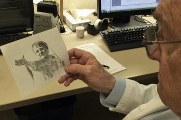 Michael LaCombe holds the card he received from a patient he treated 50 years ago. (Courtesy of Michael LaCombe)