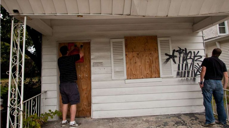 Developer Tom Moses (left) loosens boards blocking the entrance to a vacant home on Phil Ellena St. in Mt. Airy. (Brad Larrison/for NewsWorks)