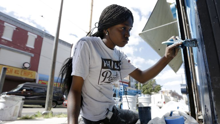 """Natalie Glover paints a store front on a commercial corridor in North Philadelphia as part of the city's renowned Mural Arts Program. Liz Dow names Mural Arts Executive Director, Jane Golden as a """"spark"""" that inspires others. (AP Photo/Matt Rourke)"""