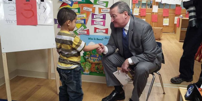 Philadelphia Mayor Jim Kenney shakes hands with a student at Kinder Academy