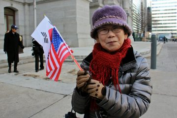 Joo Hwan Yi of Philadelphia waves the flags of the United Statesa and the Republic of Korea to celebrate Korean American Day. (Emma Lee/WHYY)