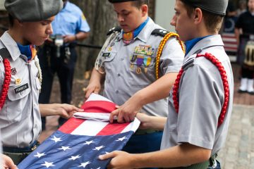 Members of the Frankford High School ROTC Program fold a flag to honor fallen police and firefighters on September 11, 2016. (Brad Larrison for NewsWorks)