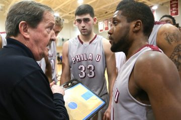 Coach Magee surrounded by his players strategizes for his 1000th win (Natavan Werbock/for NewsWorks)