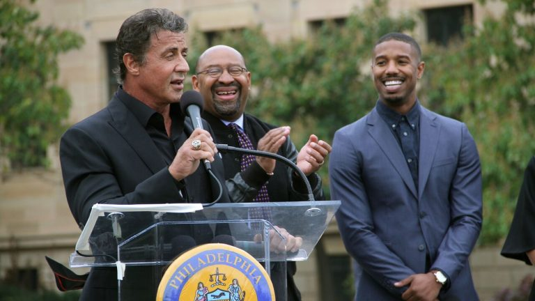 Sylvester Stallone speaks to a crowd at the top of the Art Museum steps about his new film, 'Creed.' Joining him ar Philadelphia Mayor Michael Nutter, center, and Michael B. Jordan, who portrays Adonis Creed in the movie opening Thanksgiving weekend. (Emma Lee/WHYY)
