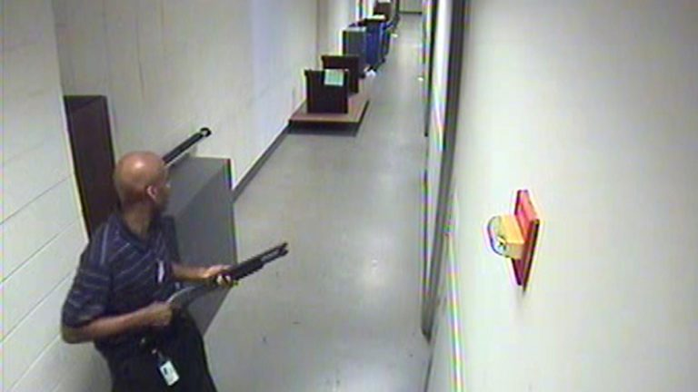 This image from video provided by the FBI, shows Aaron Alexis carrying a Remington 870 shotgun inside a Navy Yard building, where he shot and killed 12 people on Monday, Sept. 16. (AP Photo/FBI)