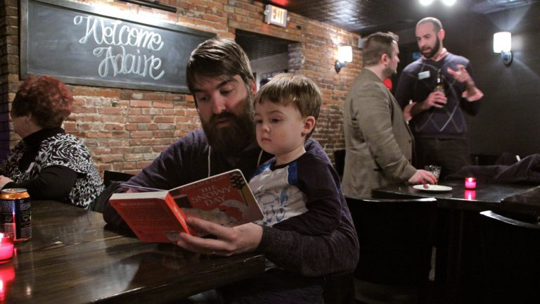 Joshua Park reads to his 2-year-old son, Jonah, during a fundraiser for Adaire Elementary School at Jerry's Bar in Fishtown. (Emma Lee/WHYY)