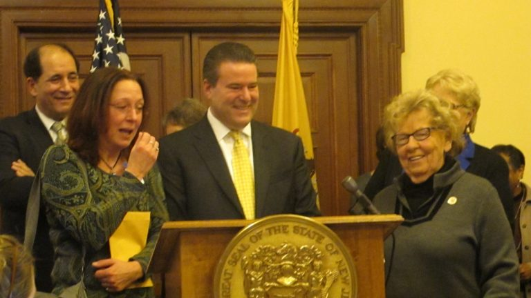 Adoptees Theresa Carroll (seond from left)and Gary Brozowski (at podium) get their birth records at a ceremony at the New Jersey Statehouse in Trenton Monday. (Phil Gregory/WHYY)