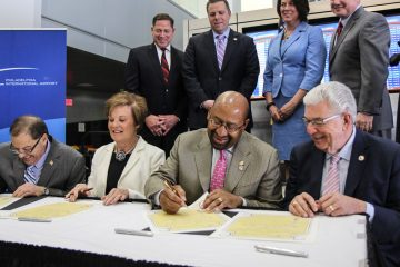 Tinicum Township Board of Commissioners president Thomas Giancristoforo, Interior School Board President Kathy Hauger, Philadelphia Mayor Michael Nutter and Delaware County Council Chairman Mario Civera sign documents symbolic of an agreement that resolves lawsuits over the Capacity Enhancement Program. (Kimberly Paynter/WHYY)