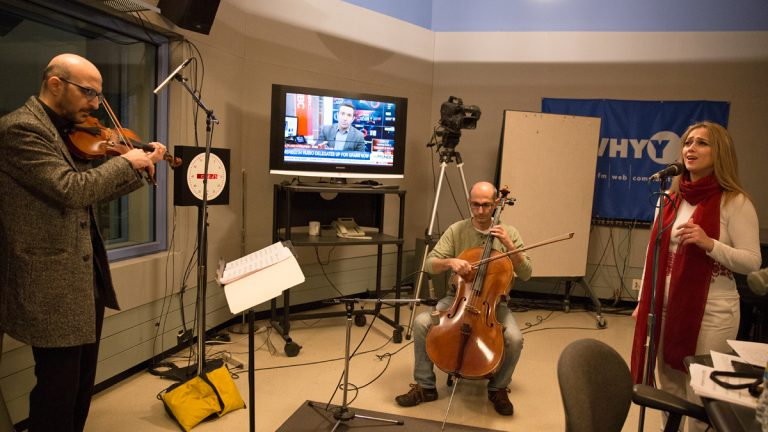 Guest singer Dalal Abu Amneh (right) performs with music director and violinist Hanna Khoury (left) and cellist Kinan Abou-afach of the Al-Bustan Takht Ensemble at WHYY Studios.  (Lindsay Lazarski/WHYY)