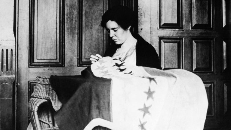 Alice Paul, chairwoman of the Nation Women's Party, takes up needle and thread to put the last stitch in the suffrage banner (c. 1932) which now has 36 stars representing the 36 states that ratified the 19th Amendment. (AP Photo)