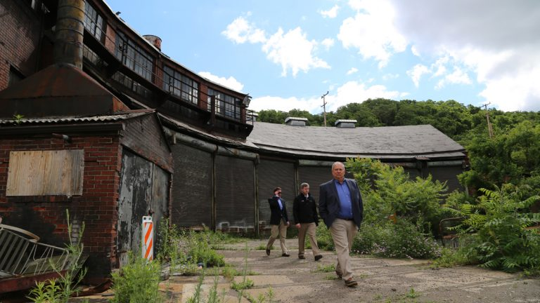 RIDC President Don Smith (right) and Tim White (center) say they're eager to see development finally begin across the 178-acre LTV Steel Hazelwood site in southeast Pittsburgh. (Megan Harris/WESA)