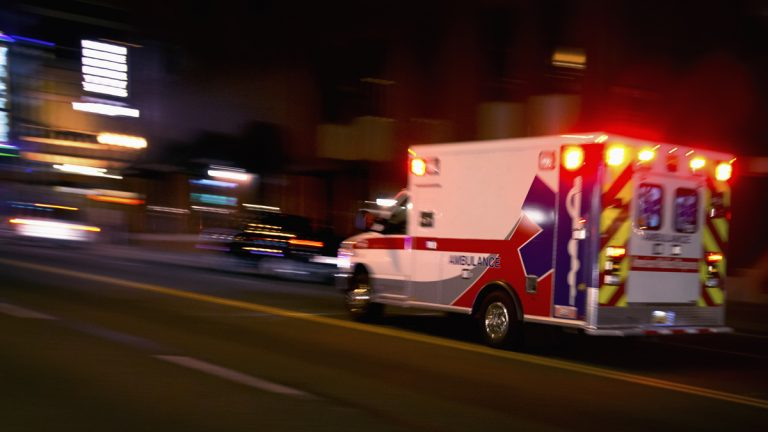 An ambulance speeds through traffic at night. (<a href=