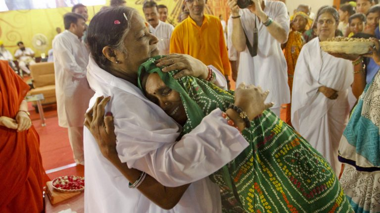 Indian spiritual leader, Mata Amritanandamayi, hugs a devotee during a function in Ahmadabad, India. Known among her followers as