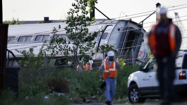 Emergency personnel walk near the scene of a deadly train wreck in Philadelphia. (Mel Evans/AP Photo)