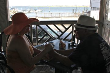 Joanne and Tom Reymont of Beach Haven West enjoy the view from the porch at Anchorage Tavern in Somers Point. (Emma Lee/WHYY)