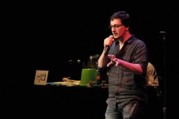 Andrew Panebianco is shown telling a story at a First Person Arts story slam. (Image courtesy of First Person Arts)