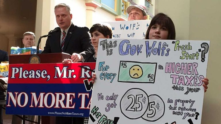 Lebanon County residents L.J. Brouillette, 10, and Samantha Brouillette, 8, hold signs as Pennsylvania Rep. Fred Keller, R-Union, speaks against the proposed sales and income tax increases in the Wolf budget plan. (Mary Wilson/WHYY)