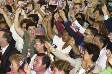 In this file photo, immigrants about to be sworn in as new U.S. citizens wave flags during the beginning of the ceremony sponsored by the Philadelphia Continental Chapter of Sons of the American Revolution in Philadelphia.(AP file photo/ Mark Stehle)