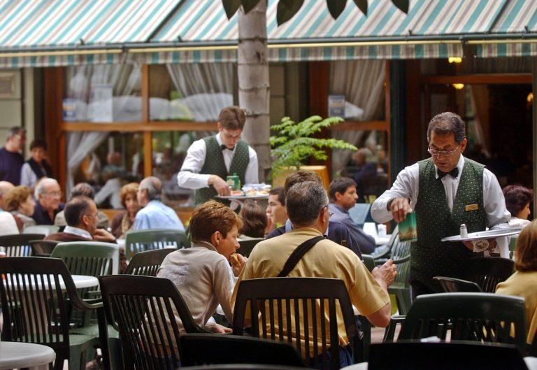 Waiters serve patrons dining in an outdoor cafe in one of Buenos Aires' swanky neighborhoods, Recoleta. Although malnutrition is rampant in the heartland and in the vast rustbelt ringing Buenos Aires, the good life goes on for part of Argentine society. (AP file Photo/Natacha Pisarenko)