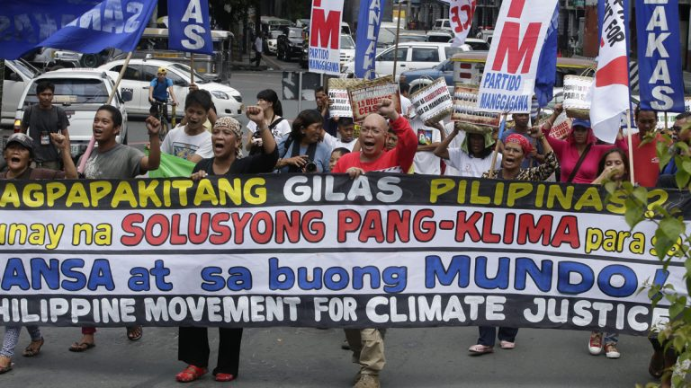 Protesters shout slogans as they march near the Presidential Palace in Manila to call on Philippine President Benigno Aquino III to focus on
