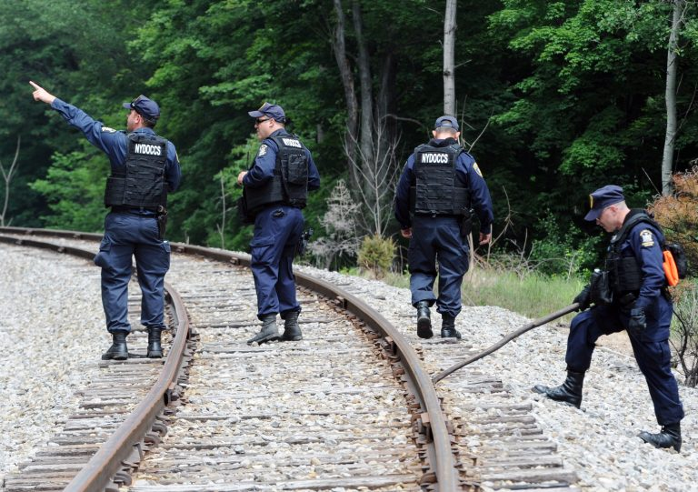New York State Department of Corrections officers search the railroad tracks after a possible sighting of the two murder convicts who escaped from a northern New York prison two weeks ago, Sunday June 21, 2015, in Friendship, N.Y. State police said a woman on Saturday reported spotting two men who resembled the convicts near a railroad line that runs along a county road. (AP Photo/Gary Wiepert)