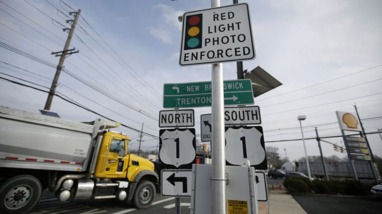 A truck passes a photo enforcement sign that is placed below a red-light camera at the intersection of Route 1 and Franklin Corner Road Tuesday in Lawrence. By midnight, Tuesday, cameras that have recorded hundreds of thousands of red-light violations in two dozen towns are scheduled to go dark as the much-scrutinized pilot program comes to an end after five years filled with controversy. (AP Photo/Mel Evans)