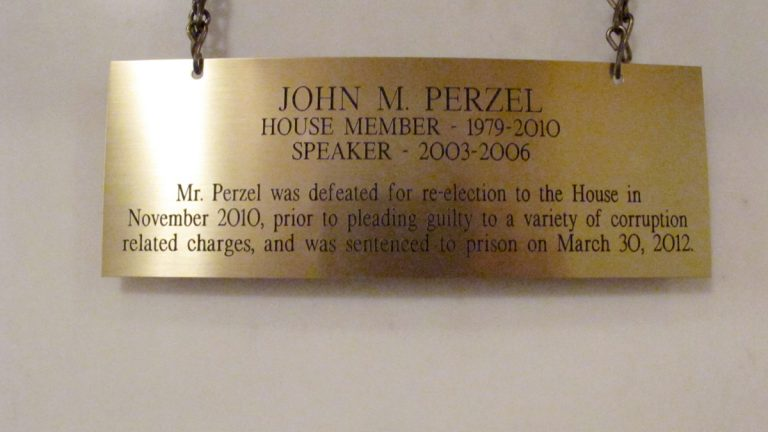 The plaque hanging in the Pennsylvania Capitol below the official portrait of former House Speaker John Perzel and three other former top state lawmakers in Harrisburg, Pa., now includes information about their criminal histories. (Marc Levy/AP Photo)
