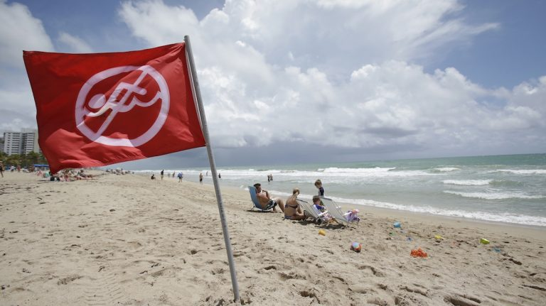 A no swimming flag flies on the beach in an area where there is a known rip current, Tuesday, May 13, 2014 in Fort Lauderdale, Fla. (AP Photo)