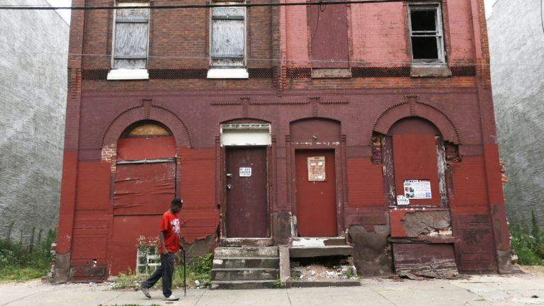 A man walks through a blighted neighborhood in Philadelphia. (Matt Rourke/AP Photo)