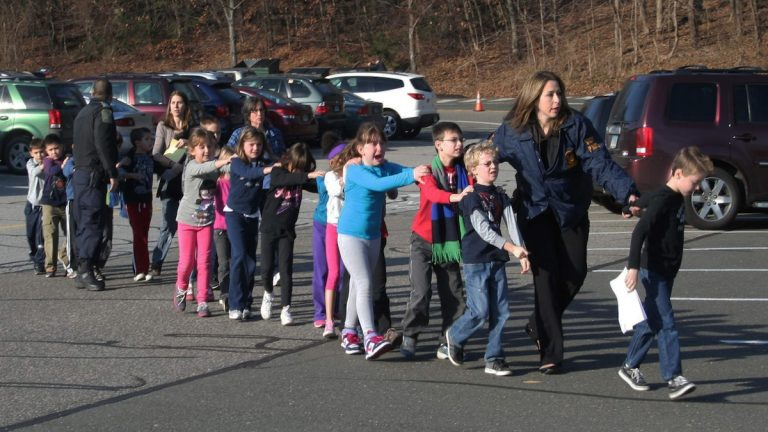 In this photo provided by the Newtown Bee, Connecticut State Police lead a line of children from the Sandy Hook Elementary School in Newtown, Conn. on Friday, Dec. 14, 2012 after a shooting at the school. Hundreds of children at the school that day survived, but the horrors have been especially difficult to overcome for some of the 6- and 7-year-olds who witnessed the bloodbath, even as the school year resumed in autumn of 2013. (AP Photo/Newtown Bee, Shannon Hicks, file)
