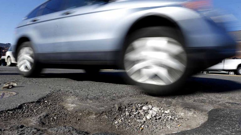 A car barely misses a pothole in Philadelphia. Since December, PennDOT has used more than 50,000 tons of patching material to fill the craters throughout the region. (AP file photo)