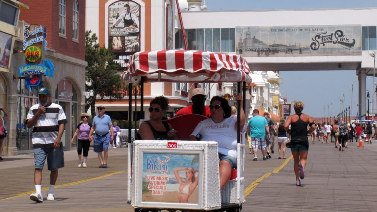 Tourists ride in a rolling chair on the Atlantic City Boardwalk. Hoping to draw visitors during October