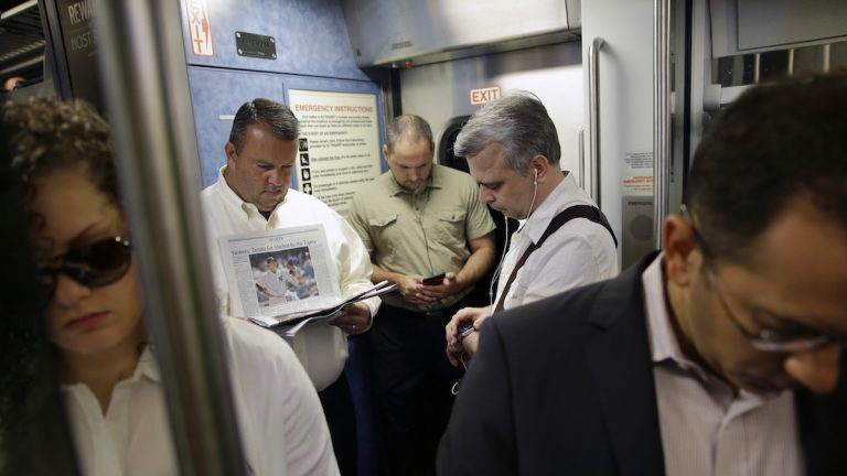 Commuters read and check their phones as they stand on a New Jersey Transit passenger train to New York. (AP Photo/Mel Evans)
