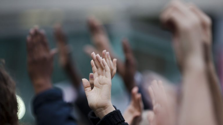 Demonstrators hold up their hands during a Wednesday protest in Philadelphia.  On Friday, protesters gathered to urge shoppers to become socially and politically active following the events in Ferguson, Missouri. (Matt Rourke/AP photo)