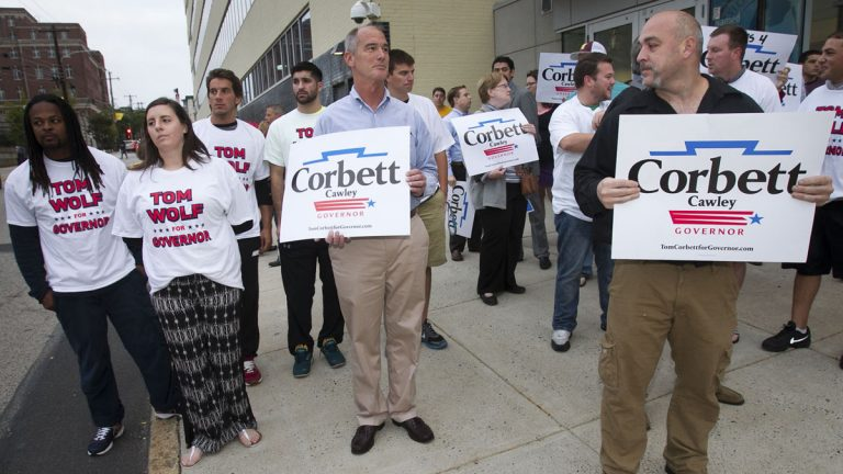 Making their sentiments known, supporters for Gov. Tom Corbett and candidate Tom Wolf gather early this month in Philadelphia as the candidates debate at
