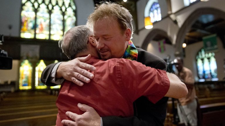 United Methodist pastor Frank Schaefer, right, hugs the Rev. David Wesley Brown Tuesday at First United Methodist Church of Germantown in Philadelphia. Schaefer, who presided over his son's same-sex wedding ceremony and vowed to perform other gay marriages if asked, can return to the pulpit after a United Methodist Church appeals panel  overturned a decision to defrock him. (AP Photo/Matt Rourke)