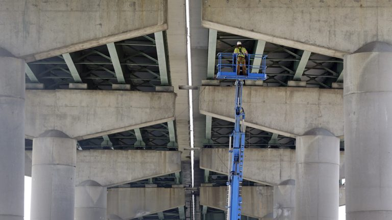 A worker inspects the underside of the Interstate 495 bridge over the Christina River near Wilmington, Del., Tuesday after it was closed due to the discovery of four tilting support columns. The closure created heavier-than-normal traffic conditions for motorists on Interstate 95, a major East Coast artery. The bridge normally carries about 90,000 vehicles a day. (AP photo/Patrick Semans