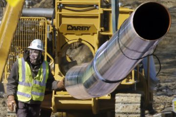 A worker guides a section of pipe while working on a shale gas pipe line Friday