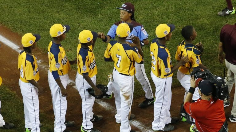Philadelphia's Mo'ne Davis, top center, shakes hands with the players from the Chicago team after Philadelphia lost 6-5 in an elimination baseball game at the Little League World Series tournament. (AP Photo/Gene J. Puskar)