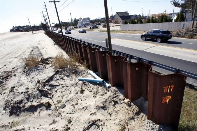 In this Oct. 13, 2013 photo, a huge steel seawall, sunken deep into the ground, is seen on the ocean side, along Route 35, in Mantoloking, N.J., in the area that was breached from the Atlantic Ocean to the Barnegat Bay a year ago during Superstorm Sandy. (AP Photo/Mel Evans)